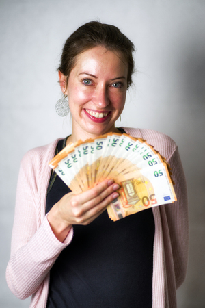 Happy woman with a lot of  money - 50 euro banknotes