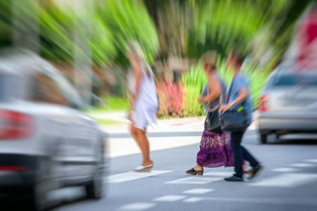 Voetgangers oversteken van een weg op zebrapad voor auto