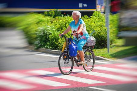 ruzomberok: RUZOMBEROK, SLOVAKIA - AUGUST 10: Senior woman crossing a road on crosswalk by bike on August 10, 2017 in Ruzomberok