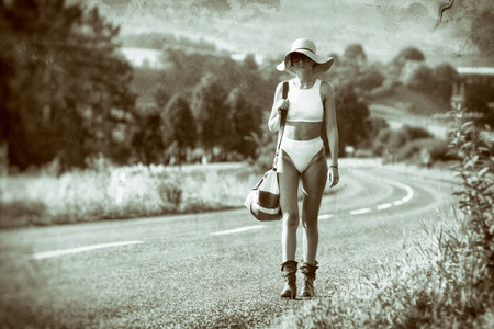 sunhat: Slim girl with sunhat and glasses walking on  road with travel bag Stock Photo