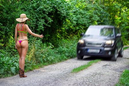 ヒッチ ハイカー道路上ビキニでスリムな女性。ヒッチハイクのコンセプト