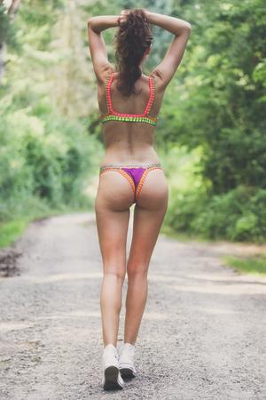 Thin girl in thong bikini bottoms walking on empty road
