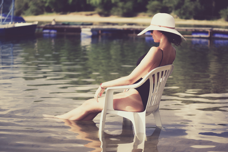 swimsuite: Slim woman in swimsuite sitting on white chair in water