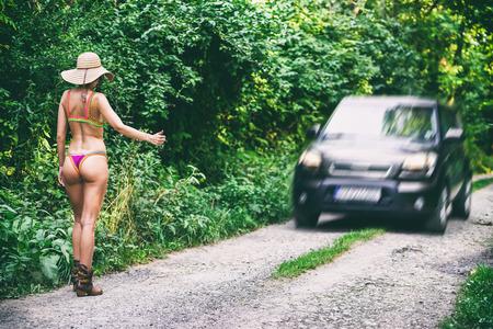 Hitchhiker slim woman in bikini on the road. Hitchhiking concept