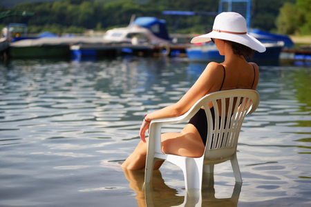 swimsuite: Slim woman in swimsuite with sunhat on head sitting on white chair in water