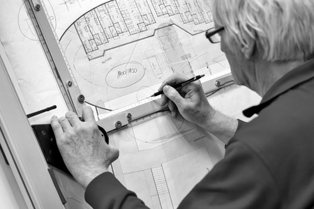 Creative engineer working with project on drawing board in office