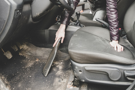 Woman cleaning interior of car with vacuum cleaner Stock Photo