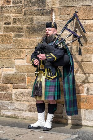 EDINBURGH, SCOTLAND - MAY 18: Scottish piper playing on bagpipe in the centre of city on May 18, 2018 in Edinburgh