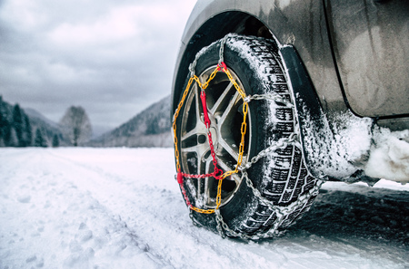 Snow chains on tire. Detail of wheel on wimter road