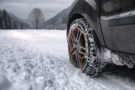 Snow chains on tire. Detail of wheel on wimter road Standard-Bild - 116671818