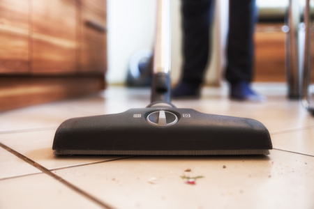 Person using vacuum cleaner while cleaning floor at home from dirt. Close up view