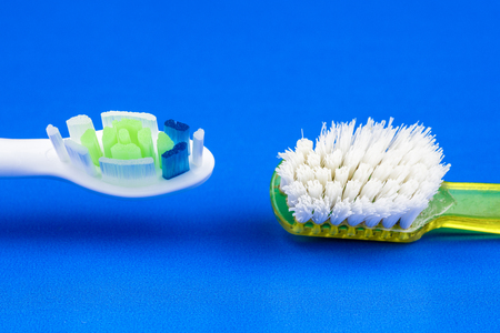 Electric vs. old toothbrush on blue background