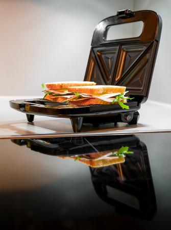 Open black sandwich toaster in kitchen