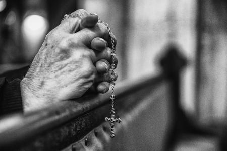 Praying senior hands with rosary in church bench Reklamní fotografie