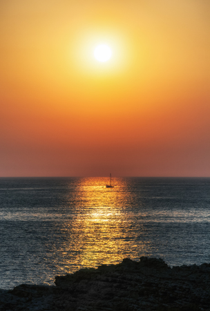 Fishing boat and colorful sunset on mediterranean sea, Malta