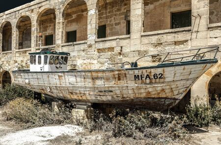 Wrecked ship and ruined house at island Comino, Malta