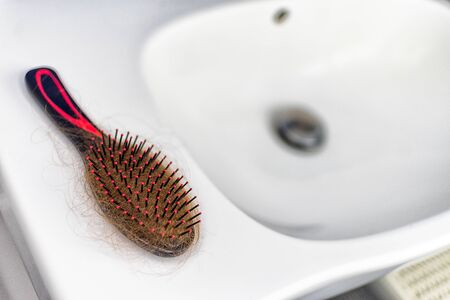 Hairbrush full of hair on the sink. Hair loss concept