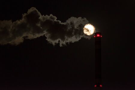 Supemoon and smoke from chimney in factory on dark sky