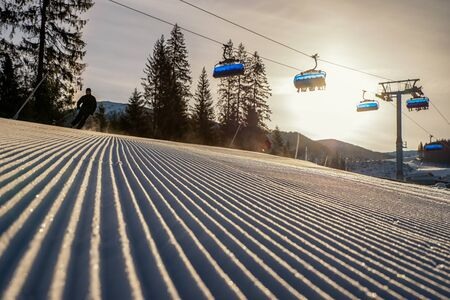 Fresh groomed snow with skier and ski lift chair at background in resort Jasna at Low Tatras mountains , Slovakia