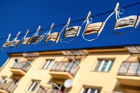Protective face masks hanging on the line in front of flat Stock Photo