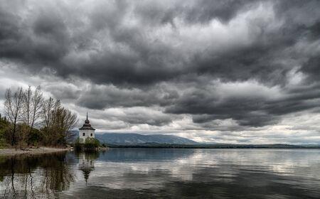 Dramatic grey clouds on the sky. Reflections on lake Liptovska Mara, Slovakia