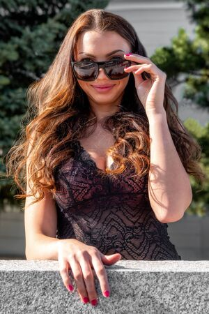 Pretty face girl with big breast and  seductive view holding sunglasses.