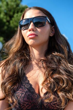 Pretty face brunette girl with big lips and breast in neckline and with sunglasses Standard-Bild
