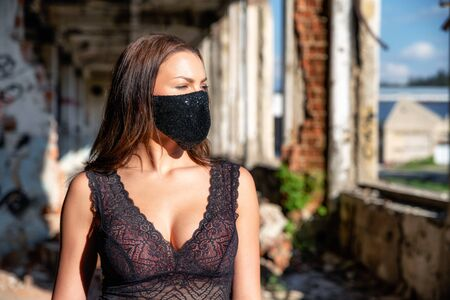 Woman with big at neckline in old factory building wearing luxury black fashion face mask due coronavirus Covid-19 protection