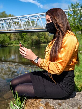 Girl with face mask sitting on the shore of the lake and looking into the cell phone. Stock Photo - 149835100