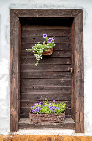 Closed wooden doors in old cottage and flowers in pot Stock Photo - 152634112
