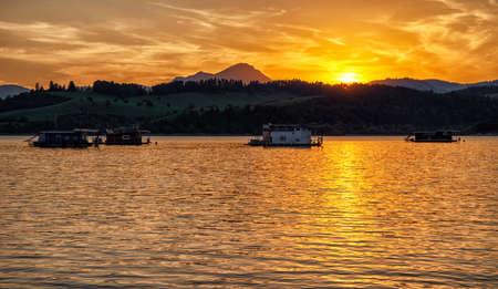 Colorful sunset  and reflection on water surface at lake Liptovska Mara, Slovakia. Houseboats on water and hill Choc at background