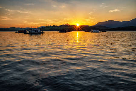 Colorful sunset  on lake Liptovska Mara, Slovakia. Houseboats on water. Sunbeams over hill Choc