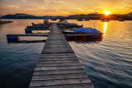 Colorful sunset  on lake Liptovska Mara, Slovakia. Boats in port
