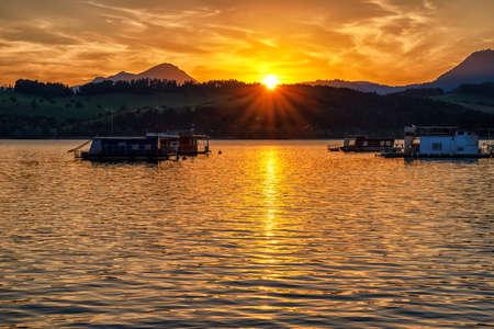 Colorful sunset  on lake Liptovska Mara, Slovakia. Houseboats on water and hill Choc at background Stock Photo - 153438379