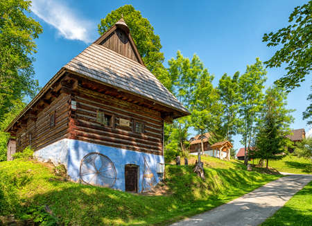 Traditional old wooden rural cottage with blue facade in village Srnacie - Dolny Kubin, Slovakia Stock Photo