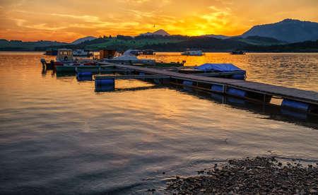 Colorful sunset  on lake Liptovska Mara, Slovakia. Orange sky and boats in port
