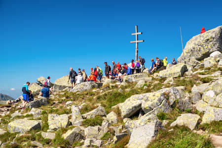 DEMANOVSKA DOLINA, SLOVAKIA - AUGUST 21, 2020: Cross on top of hill Dumbier in Low Tatras mountains full of hikers