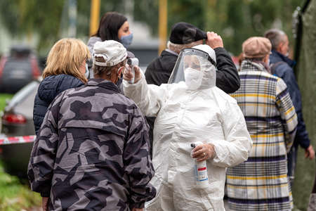 RUZOMBEROK, SLOVAKIA - OCTOBER 16, 2020:  Woman doctor in protective suit and shield checked a temperature of people with thermometer in front of checkpoint during second wave of coronavirus Covid-19 Redakční