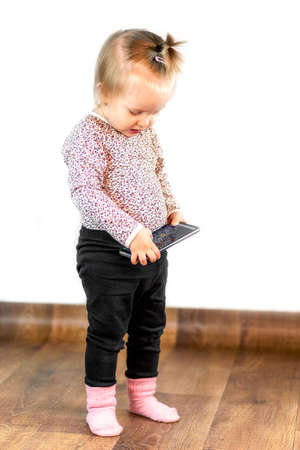 Little girl playing game on smarthphone at interior Foto de archivo