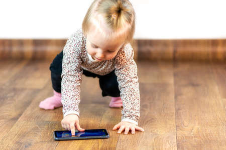 Baby girl playing game on smarthphone at interior