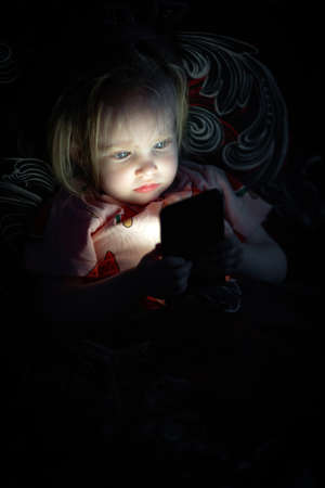 Small baby girl lying on bed and looking on smarthphone screen at night. Foto de archivo