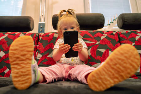 Little baby girl sitting on sofa, holding smarthphone and watching cartoons