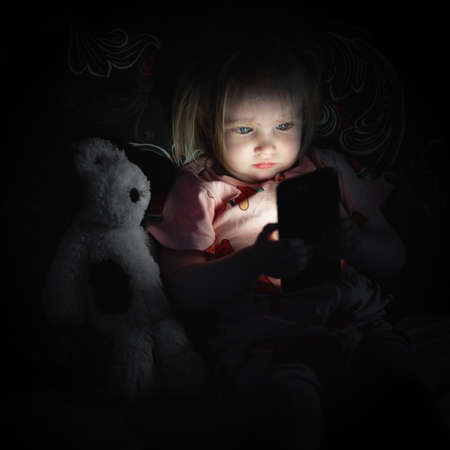 Small baby girl lying on bed and looking on smarthphone screen at night.