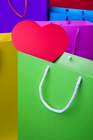 Colourful paper shopping bags with red heart  Yellow, violet, red, blue, pink and green shopping bags photo