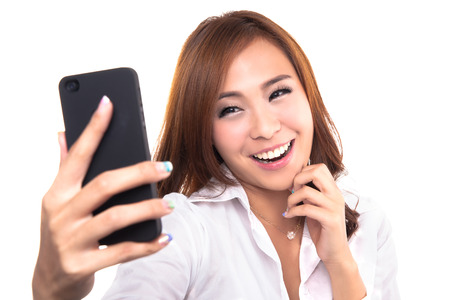 snap: Pretty girl take a self portrait with her smart phone  Asian girl selfie, isolated on white background Stock Photo