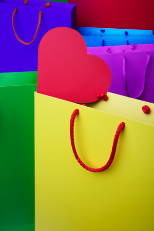 Colorful paper shopping bags with red heart  - Yellow, violet, red, blue and green shopping bags photo