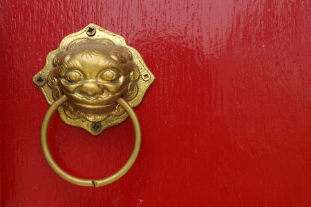 Red chinese door with a liondragon head photo