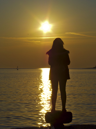 siluetas de mujeres: Puesta del sol de la muchacha por el mar