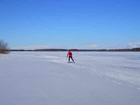 Cross country skier skiing on a frozen lake. Winter sports. Stock Photo