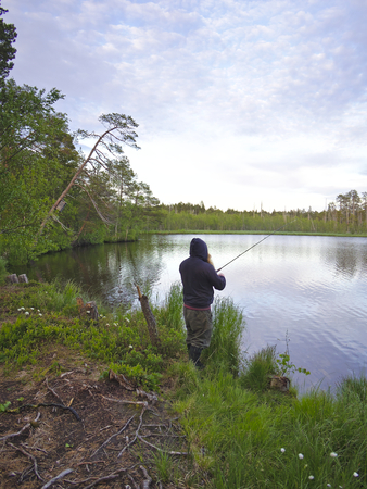 Fisherman casting a bait by a small lake. Stock Photo